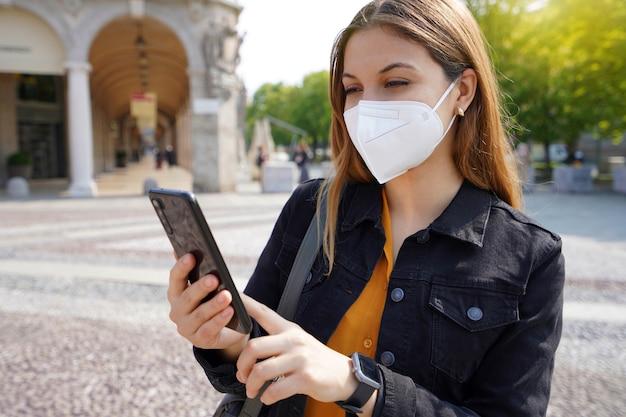 Młoda bizneswoman nosząca maskę kn95 ffp2 używająca smartfona na zewnątrz