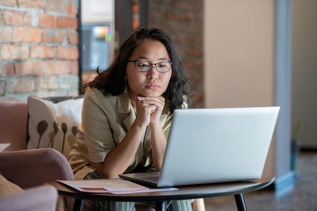 Młoda bizneswoman ogląda wideo online lub komunikuje się z kimś