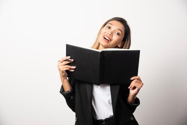Młoda bizneswoman pokazuje czarny schowek.