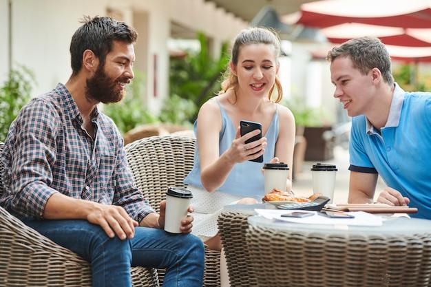 Młoda bizneswoman pokazuje kolegom aplikację mobilną