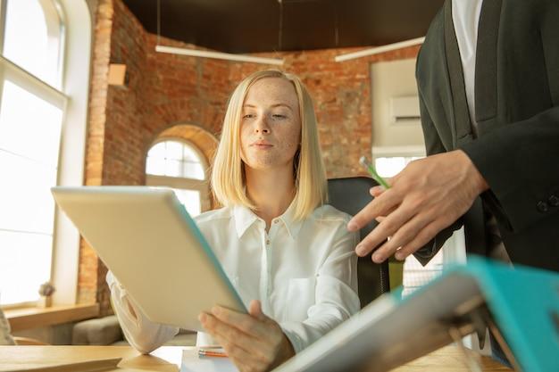 Młoda bizneswoman porusza się w biurze, uzyskując nowe miejsce pracy. młoda pracownica biura po awansie spotyka swoją koleżankę lub kolegę z pracy, korzystając z pomocy. biznes, styl życia, nowa koncepcja życia.