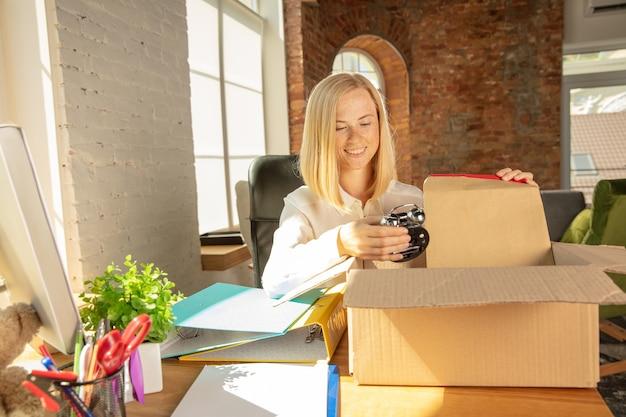 Młoda bizneswoman porusza się w biurze, uzyskując nowe miejsce pracy. młody kaukaski pracownik biurowy wyposaża nową szafkę po awansie