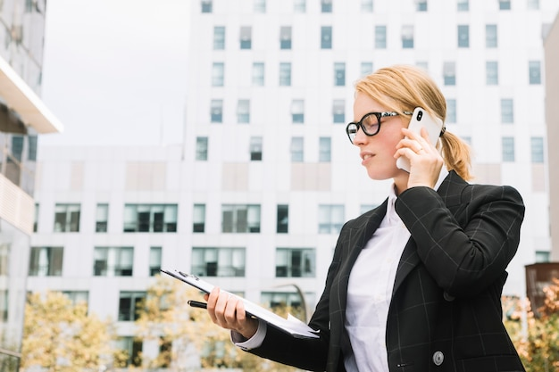 Młoda bizneswoman pozycja na zewnątrz korporacyjnych budynków opowiada na telefonie komórkowym