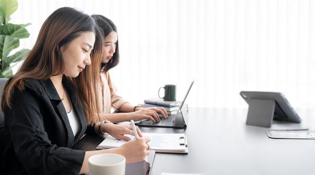 Młoda bizneswoman pracuje razem w nowoczesnym pokoju biurowym.