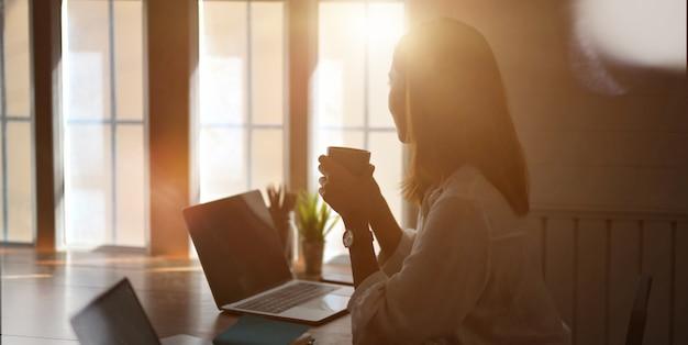 Młoda bizneswoman pracuje z laptopem i pije filiżankę kawy