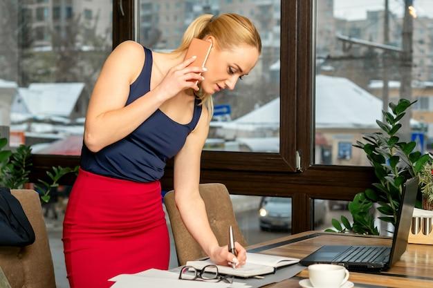 Młoda bizneswoman rozmawia przez telefon, pisanie notatek stojących w biurze lub kawiarni