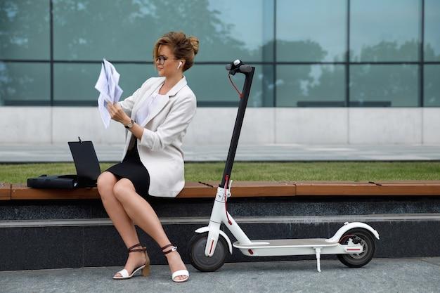 Młoda bizneswoman siedzi na ławce z dużą ilością papierowych dokumentów i skuter elektryczny obok niej