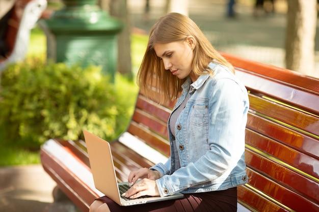 Młoda bizneswoman siedzi w parku i pracuje z laptopem