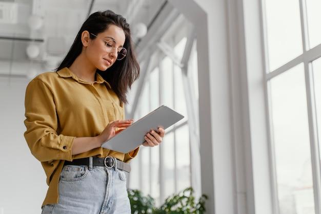 Młoda bizneswoman sprawdza jej tabletkę z miejsca na kopię