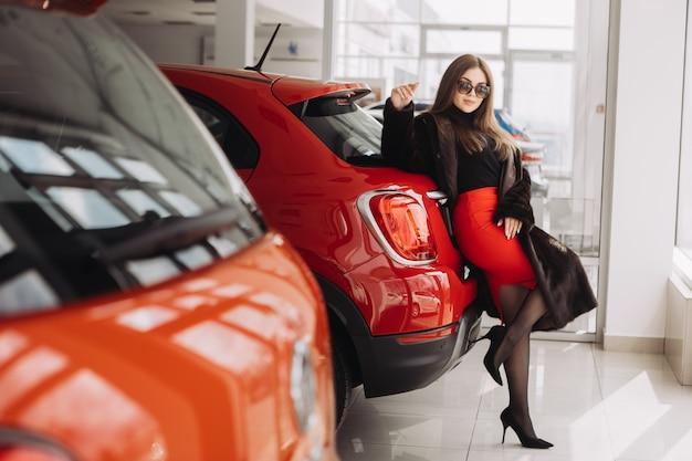 Młoda bizneswoman testuje samochody w sklepie samochodowym