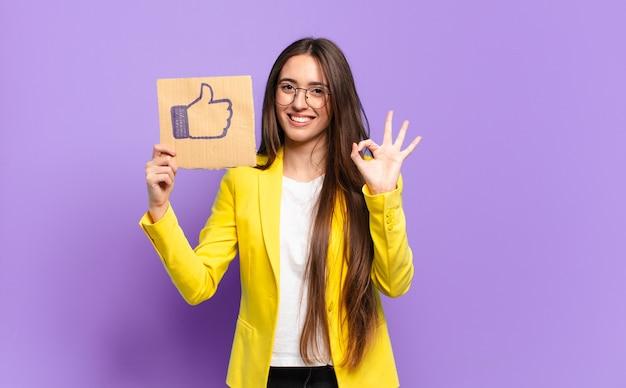Młoda bizneswoman trzyma media społecznościowe jak symbol