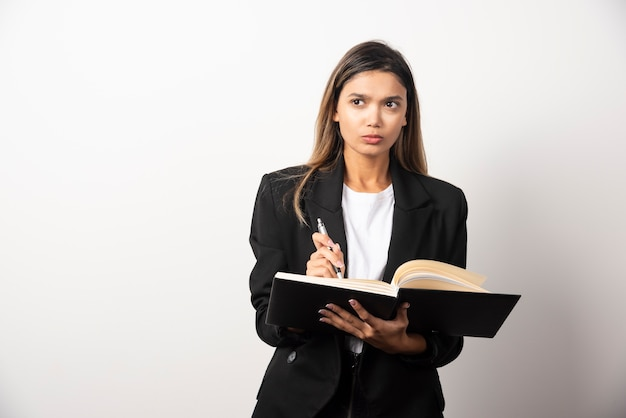 Młoda bizneswoman trzyma otwarty schowek z ołówkiem.