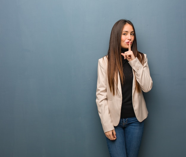 Młoda bizneswoman trzyma w tajemnicy lub prosi o ciszę
