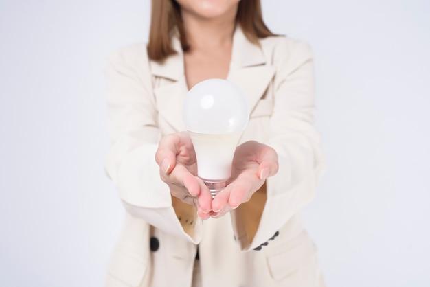 Młoda bizneswoman trzyma żarówkę w garniturze na białym tle studio