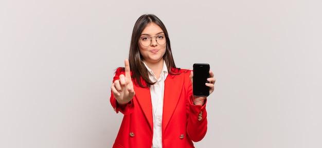 Młoda bizneswoman uśmiecha się dumnie i pewnie, triumfalnie tworząc pozę numer jeden, czując się jak lider