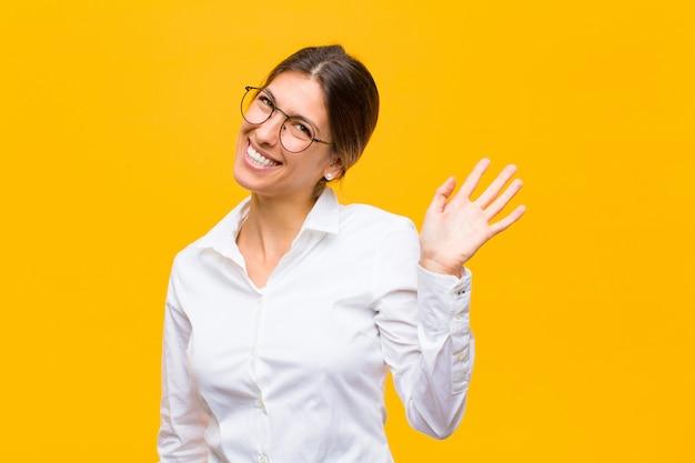 Młoda bizneswoman uśmiecha się radośnie i wesoło, macha ręką, wita i wita lub żegna się z pomarańczową ścianą