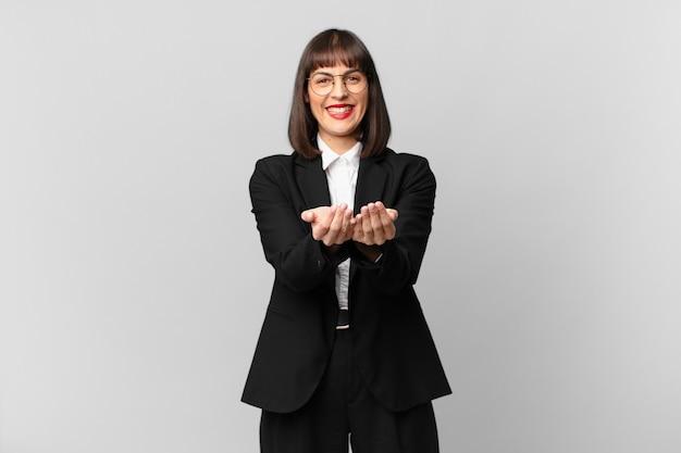 Młoda bizneswoman uśmiecha się radośnie z przyjaznym, pewnym siebie, pozytywnym spojrzeniem, oferując i pokazując przedmiot lub koncepcję
