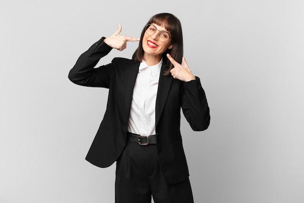 Młoda bizneswoman uśmiechnięta pewnie, wskazując na swój szeroki uśmiech, pozytywna, zrelaksowana, zadowolona postawa