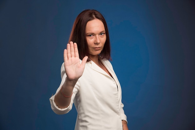 Młoda bizneswoman w białej marynarce mówi do widzenia.