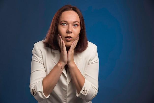 Młoda bizneswoman w białej marynarce patrząc na jej twarz.