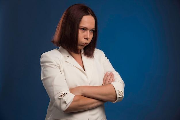 Młoda bizneswoman w białej marynarce wygląda na przygnębioną.