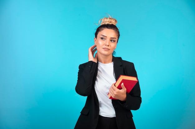 Młoda bizneswoman w czarnej marynarce trzyma książkę zadań.