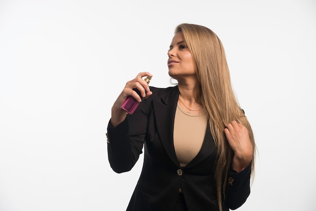 Młoda bizneswoman w czarnym garniturze nakłada perfumy na szyję.