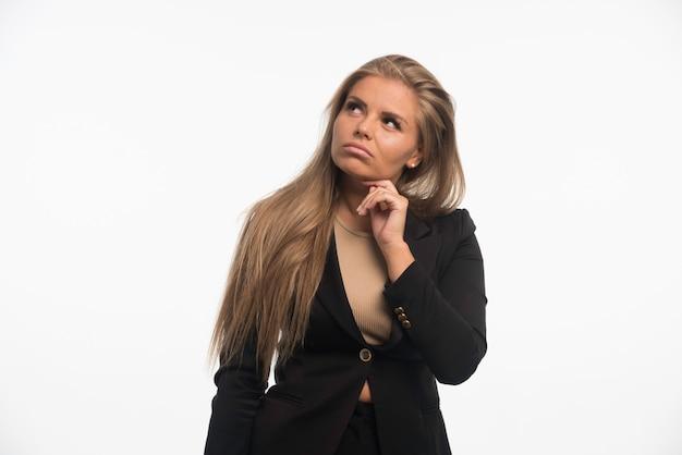 Młoda bizneswoman w czarnym garniturze wygląda wątpliwie.