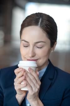 Młoda bizneswoman w mundurze z kawą