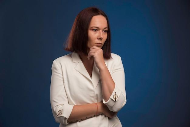 Młoda bizneswoman w planowaniu białej marynarki.