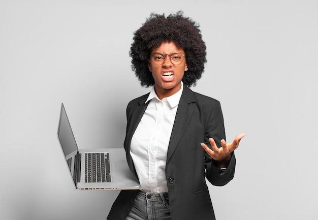Młoda bizneswoman w stylu afro wygląda na złą, zirytowaną i sfrustrowaną, krzyczącą wtf lub co jest z tobą nie tak. pomysł na biznes