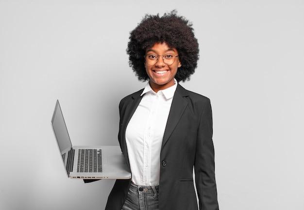 Młoda bizneswoman w stylu afro wyglądająca na szczęśliwą i mile zaskoczoną, podekscytowana zafascynowaną i zszokowaną miną. pomysł na biznes