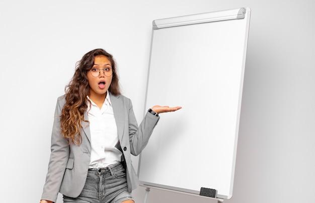 Młoda bizneswoman wygląda na zaskoczoną i zszokowaną, z opadającą szczęką, trzymając przedmiot otwartą ręką z boku