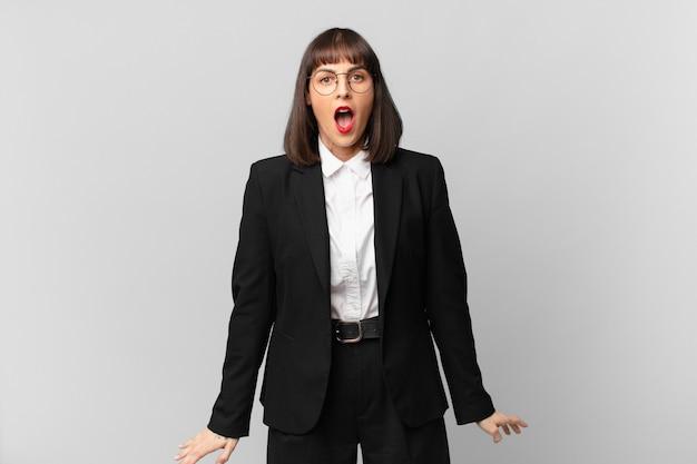 """Młoda bizneswoman wyglądająca na bardzo zszokowaną lub zaskoczoną, patrząca z otwartymi ustami, mówiąca """"wow"""