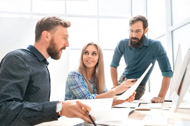 Młoda bizneswoman wyjaśnia coś swoim kolegom. biurowe dni powszednie