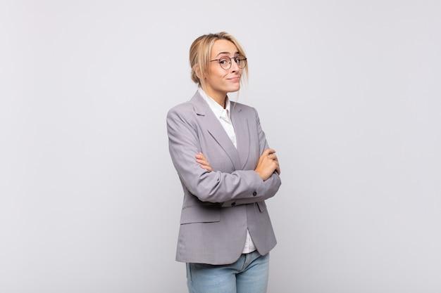 Młoda bizneswoman wzrusza ramionami, czuje się zdezorientowana i niepewna, wątpi ze skrzyżowanymi ramionami i zdziwiona