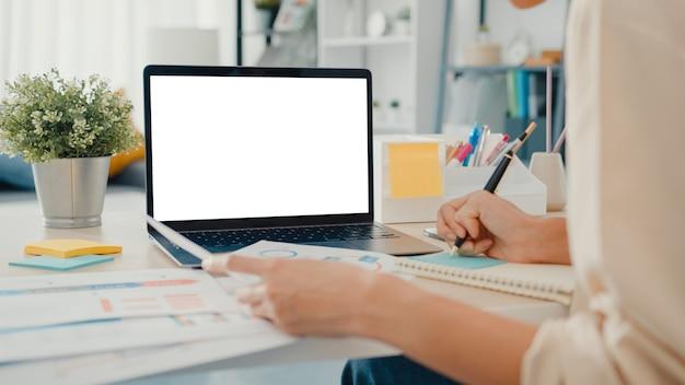 Młoda bizneswoman z azji używa smartfona z pustym białym ekranem podczas inteligentnej pracy z domu w salonie
