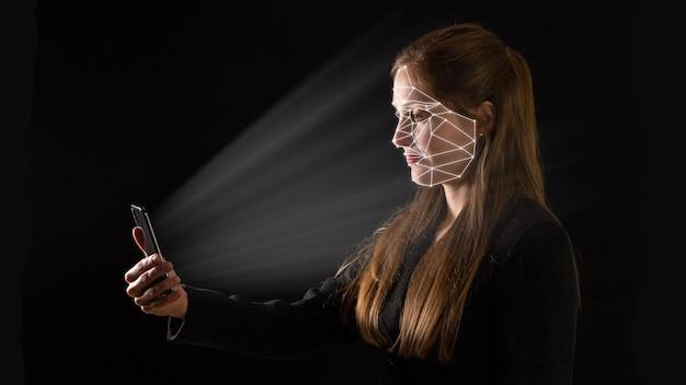Młoda bizneswoman z kaukazu korzystająca z technologii biometrycznej w swoim telefonie