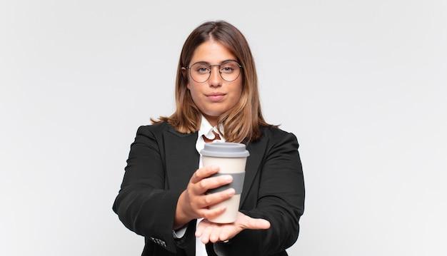 Młoda bizneswoman z kawą uśmiecha się radośnie z przyjaznym, pewnym siebie, pozytywnym spojrzeniem, oferuje i pokazuje przedmiot lub koncepcję