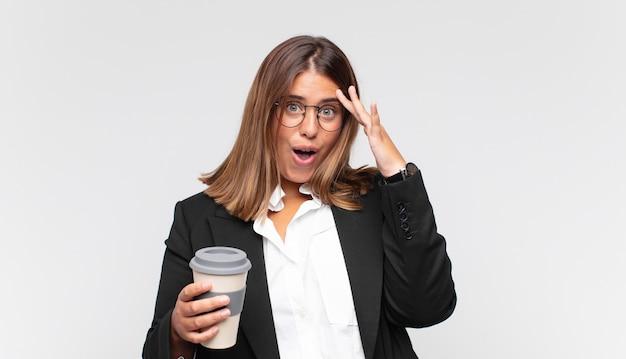 Młoda bizneswoman z kawą wyglądająca na szczęśliwą, zdziwioną i zaskoczoną, uśmiechniętą i uświadamiającą sobie niesamowite i niewiarygodnie dobre wieści