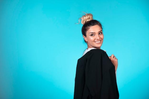 Młoda bizneswoman z kok trzyma czarną marynarkę i uśmiecha się.