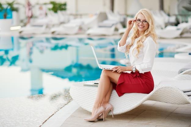 Młoda bizneswoman zdalnie pracuje na laptopie na swoim podwórku w domu.
