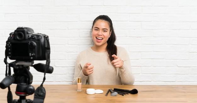 Młoda blogerka, azjatka, nagrywa film instruktażowy, wskazując na ciebie palcem