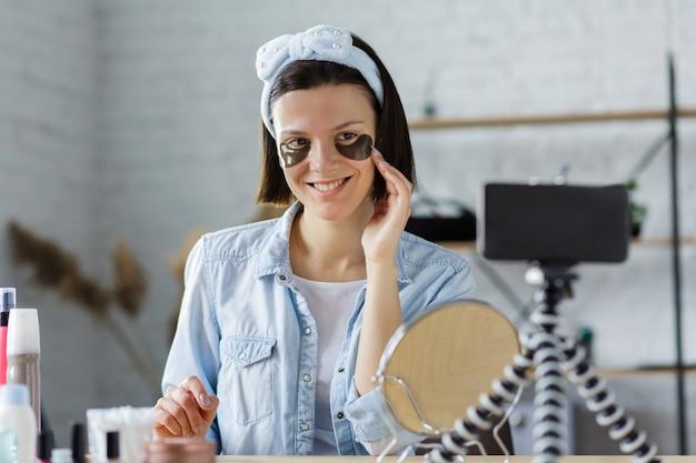 Młoda blogerka nagrywa film instruktażowy dla swojego bloga o kosmetykach. blogowanie, wideoblog, koncepcja pielęgnacji skóry.