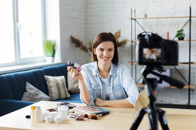 Młoda blogerka nagrywa film instruktażowy dla swojego bloga o kosmetykach. vlogger testuje lakier do paznokci i transmituje wideo na żywo do sieci społecznościowej w domu. blogowanie, wideoblog, koncepcja makijażu.