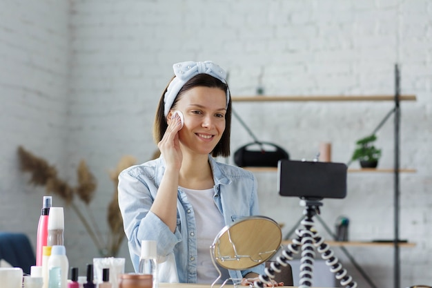 Młoda blogerka nagrywa film instruktażowy dla swojego bloga o kosmetykach. vlogger testuje wodę micelarną, transmituje wideo na żywo do sieci społecznościowej w domu. blogowanie, wideoblog, koncepcja pielęgnacji skóry.