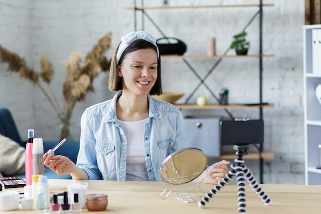 Młoda blogerka nagrywa film instruktażowy na swoim blogu kosmetycznym o kosmetykach