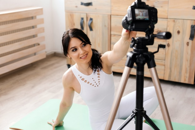 Młoda blogerka nagrywa wideo sportowe w domu