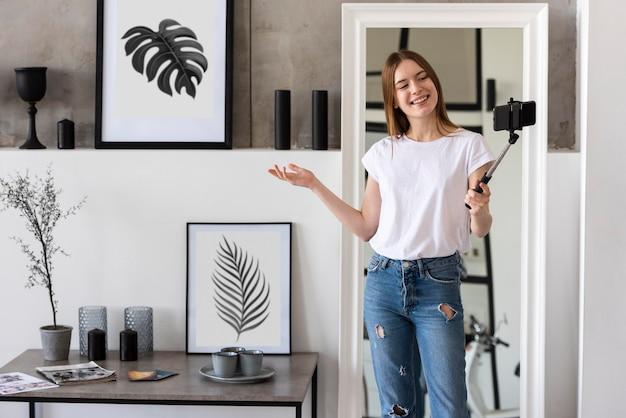 Młoda blogerka nagrywająca swój dom za pomocą smartfona