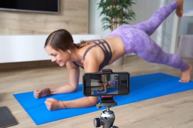 Młoda blogerka nagrywająca wideo sportowe w domu, robiąca jogę w salonie z laptopem